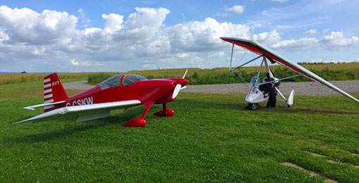 Fixed and flexwing aircraft parked at Brown Shutters Farm Airfield